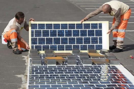 A stretch of solar panel being placed on a roadway in France